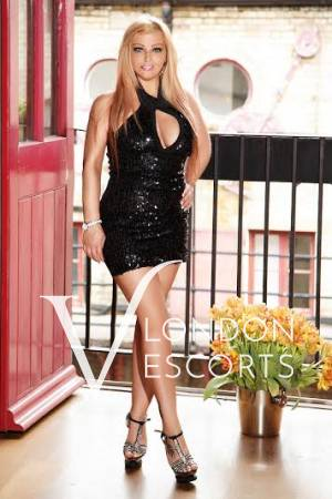 Blonde escort Lina wearing black dress in front of a balcony