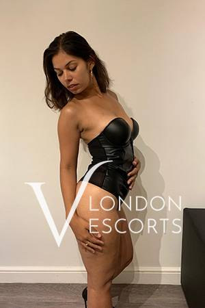 Brunette escort Alana dressed in black leather corset